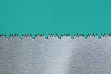 steel teeth on a gray hacksaw on a green background