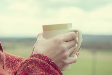 Young girl wrapped in plaid with cup of coffee in hands