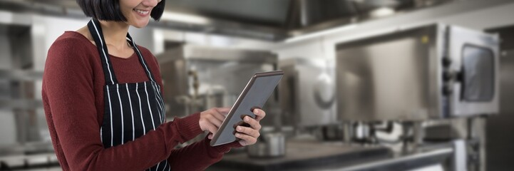 Composite image of waitress using digital tablet against white