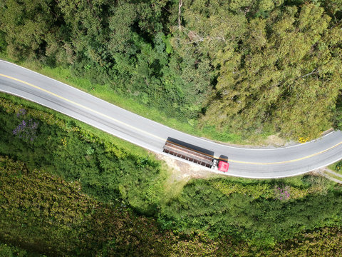 A drone upper view picture of a curve road in brazil with a truck