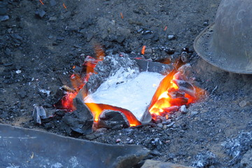 The melting of metal cans in a fire to mould it into a frying pan, Num village, Nepal
