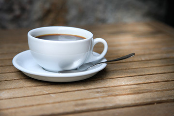 White cup with brown coffee on a wooden table.