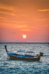 Longtail boats at Sunset Beach, Ko Lipe, Satun Province, Thailand. Traditional long tail boat and rising sun.