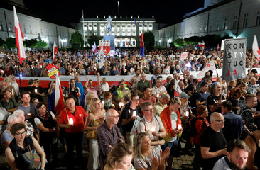 """People gather during the """"Chain of lights"""" protest against judicial overhaul in Warsaw"""