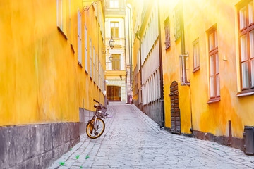 The narrow cobblestone street with a bicycle and yellow medieval houses of Gamla Stan historic old center of Stockholm at summer sunny day.