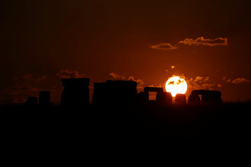 The sun sets behind the Stonehenge stone circle in southwest Britain