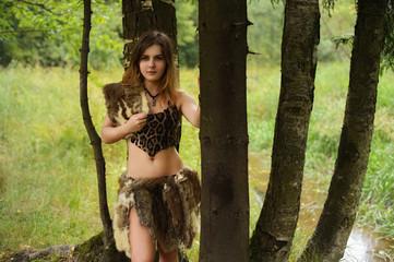 Girl in fur skins standing in the woods between the trees