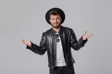 A young cheerful man with a beard in a stylish black leather jacket and hat on a gray background. Smiling at the good news
