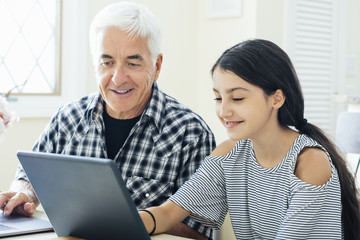Smiling girl using digital tablet with grandfather while sitting at home