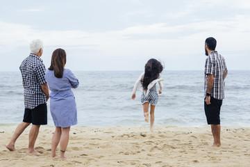 Full length of family looking at girl running towards sea at beach