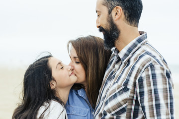 Mature man looking at loving woman kissing daughter at beach