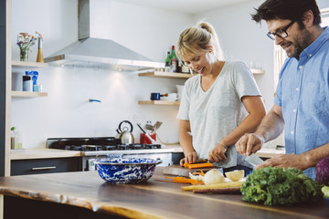 Mid Adult couple cooking together in kitchen
