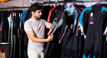 man holding and choosing suit for surfing in the shop