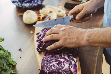Cropped image of man's hands cutting purple cabbage on board at kitchen island