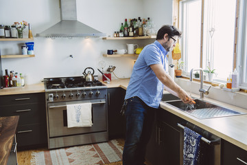 Mature man washing carrot while standing at kitchen counter in home