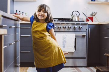 Portrait of cute little girl smiling while standing in kitchen