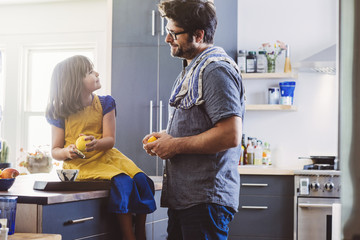 Mature father looking at daughter talking while sitting on kitchen island