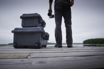 Low section of man holding camera by suitcases on wooden pier