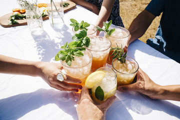 Hands holding cold drinks with basil garnish