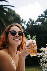 Smiling young woman wearing sunglasses while enjoying drink in yard