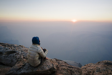 High angle view of woman sitting on cliff by mountains against sky during sunset