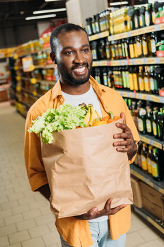 smiling african american male shopper holding paper bag with fruits and vegetables in supermarket
