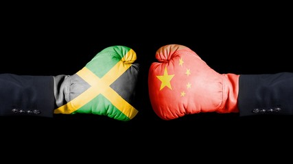 Male hand in Boxing gloves with Jamaica and China flags. Jamaica versus China concept.