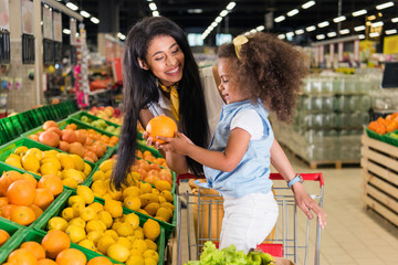 smiling african american woman giving grapefruit to little daughter in supermarket