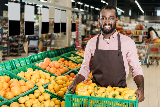 happy african american male shop assistant in apron holding box with bell peppers in grocery store