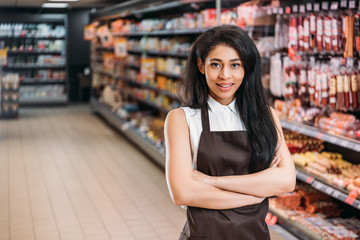 selective focus of african american female shop assistant in apron with crossed arms looking at camera in supermarket