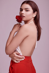 Wall Mural - Elegant beautiful woman in a red fashionable suit with rose