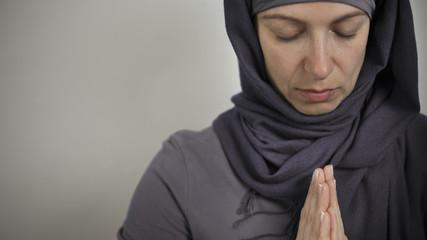 A Muslim woman prays in a hijab. Copy space.