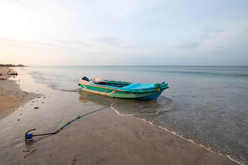 Small fishing boat with anchor at sunset on Nilaveli beach in Sri Lanka Asia