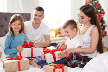 Happy parents and children exchanging gifts on Christmas morning at home