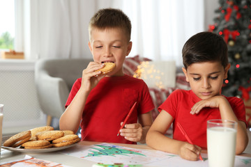 Little boy eating cookies while his friend drawing picture at home. Children celebrating Christmas