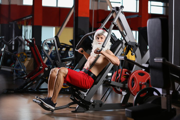 Young muscular man in Santa costume training at gym