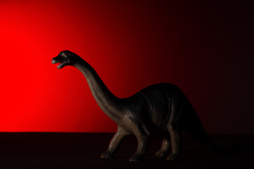 Diplodocus with spot light on the head and red light on background no logo and no trademark
