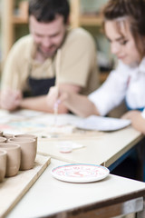 Blurred Image of Two Caucasian Ceramists Glazing Ceramic Clay Tiles in workshop Together.
