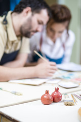 Two Ceramists Decorating Clay Crafts In workshop. Blurred Background.