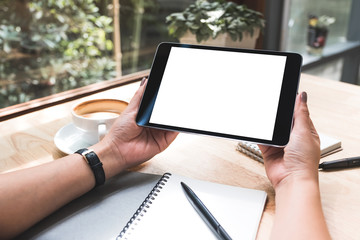 Mockup image of a woman's hands holding black tablet pc with white blank screen with notebook and coffee cup on table