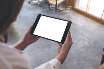 Top view mockup image of a woman sitting and holding black tablet pc with blank white desktop screen in cafe