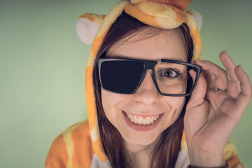 The girl in the broken sun protection glasses in a bright children's pajamas in the form of a kangaroo. emotional portrait of a student. costume presentation of children's animator. Slippers in the fo