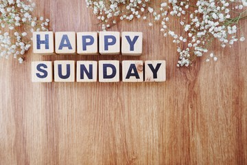 happy sunday alphabet letters on wooden background