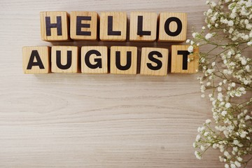 august alphabet letters on wooden background