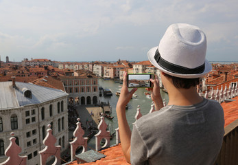 boy with a white hat photographs the city of Venice