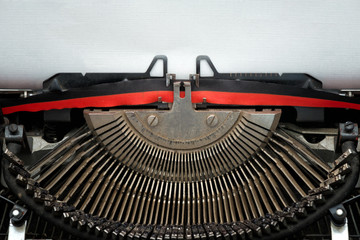 close vintage typewriter black and red ribbon and typebars ready to type on a blank textured sheet