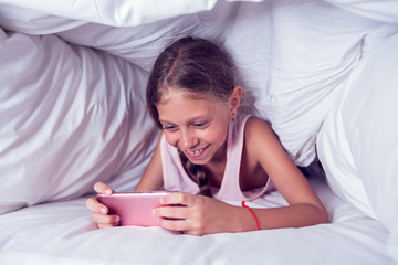 Happy Girl Looking At Mobile Phone While Lying Under Blanket On The Bed