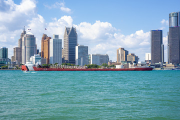 DETROIT, MI - AUGUST 18, 2015:  View of barge navigating the Detroit river with General Motors Building and downtown Detroit in the background.