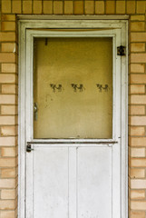 An old faded yellow farmhouse door with cow stencils