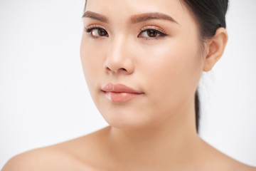 Young pretty Asian woman with clear skin looking at camera on white background